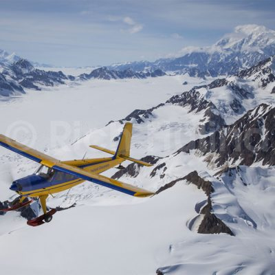 Icefield Discovery's Helio Courier C-GXFB flies over the Kluane National Park with Mt. Logan in the distance, Canada's highest peak.